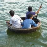 3 vissers in een gevlochten badkuipje, onderweg van de wal naar hun boot